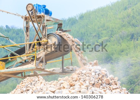 closeup conveyor and pile of quarry stone for lime industry - stock photo