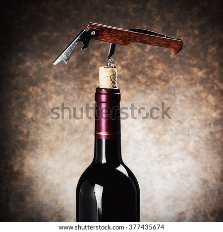 Closeup corkscrew in a wine bottle on a brown background with vignette - stock photo