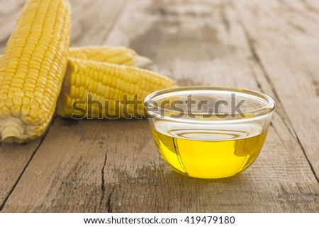 Closeup, corn oil on a wooden table. - stock photo