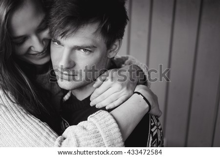 closeup couple girl and man in love Scandinavian style, sweater with deer, kissing and holding hands close  a beautiful young blond hair