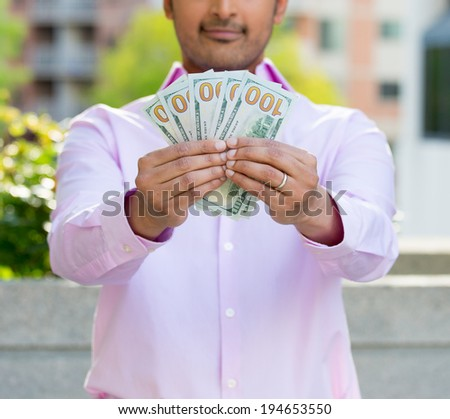 Closeup cropped portrait, happy, successful young business man holding, showing money hundred dollar bills in hand, isolated background of trees, building. Financial reward - stock photo