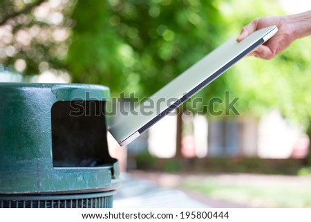 Closeup cropped portrait of someone tossing old notebook computer in trash can, isolated outdoors green trees background - stock photo