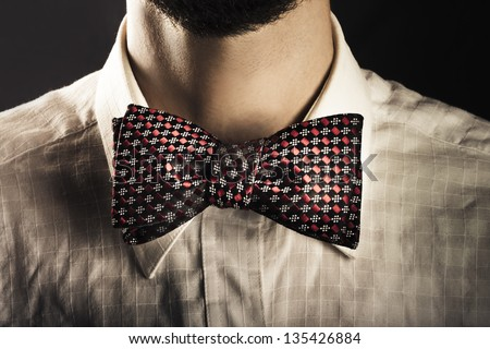 Closeup cropped portrait of the neck of a fashionable bearded man wearing an elegant patterned bow tie