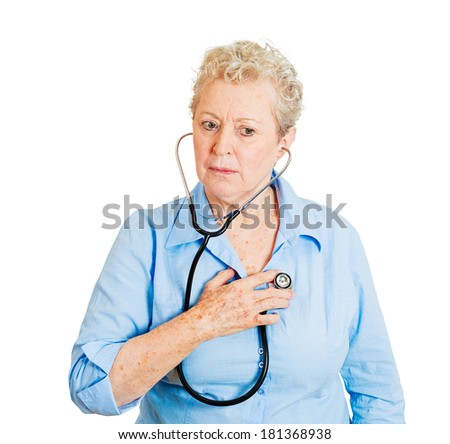 Closeup cropped portrait senior woman, business person, worker listening to her heart with stethoscope isolated on white background. Preventive medicine, financial condition, self assessment concept - stock photo