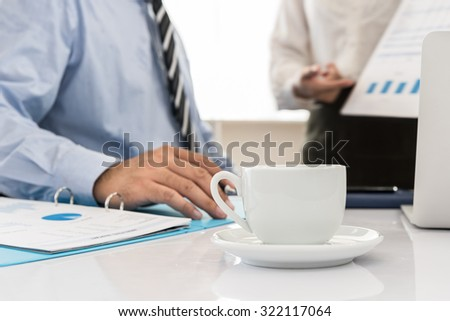 closeup cup coffee on desk with two business people are meeting - stock photo
