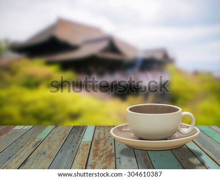 closeup cup of coffee on the windowsill on roofs background