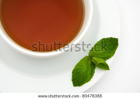 Closeup cup of tea with mint leaves over white background