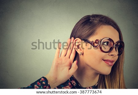 Closeup curious funny looking woman holds her hand near ear and listens isolated on gray wall background. Human face expression emotion reaction body language  - stock photo