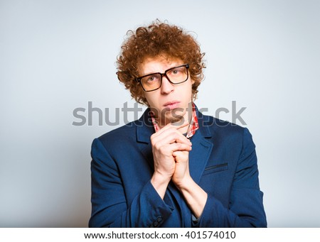 closeup curly man asks for forgiveness, isolated on background - stock photo