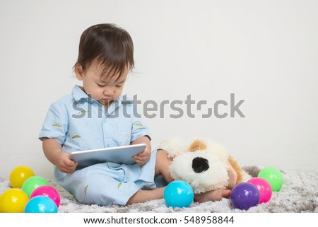 Closeup cute asian kid look at the tablet at home on gray carpet with doll and colorful ball and cement wall textured background with copy space