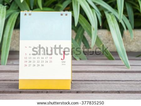 Closeup cute calendar in june on blurred garden view background - stock photo