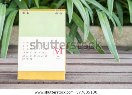 Closeup cute calendar in may on blurred garden view background - stock photo