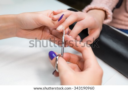 Closeup cuticle clipping, cutting skins manicure treatment with the central finger client in salon nail salon or spa. Hand on the black professional pillow.  - stock photo