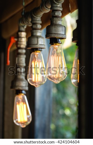 Closeup decorated light bulb hanged on water pipe
