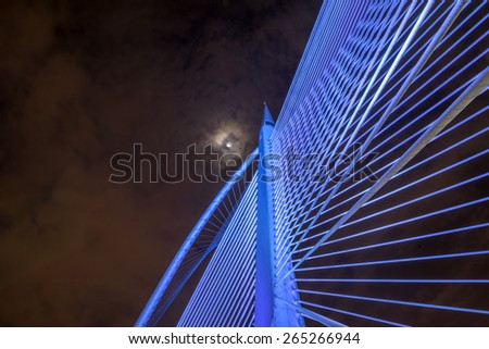 Closeup design of Sri Wawasan bridge at Putrajaya, Malaysia.  A night view showing blue color light on the steel structure with the moon and sky at the background. - stock photo
