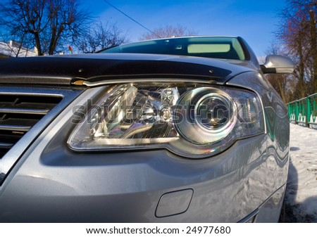 Closeup detail of a headlight on a modern vehicle with metallic paint - stock photo