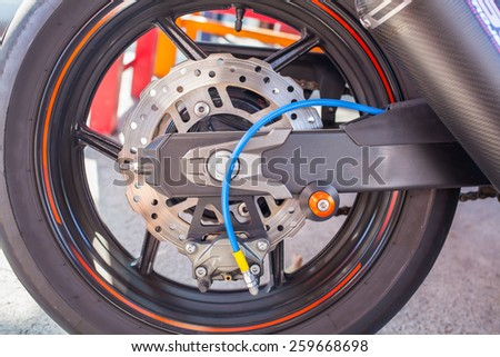 Closeup detail of a motorcycle's back wheel and brake disc - stock photo