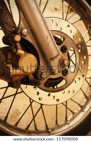 Closeup detail of a motrotcycle front wheel with black spikes and brake disc - stock photo