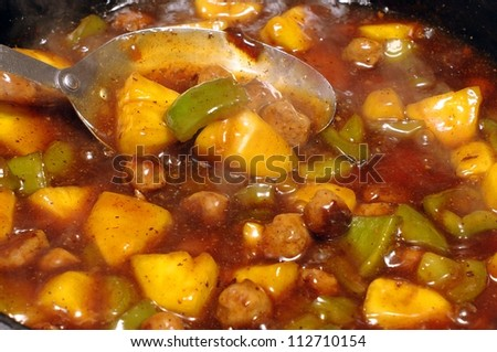 Closeup detail of a pan of sweet and sour chicken with pineapple, green pepper, and spices cooking, with some thin wisps of steam visible - stock photo