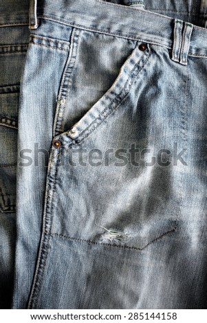 Closeup detail of a washed out blue jeans pocket - stock photo