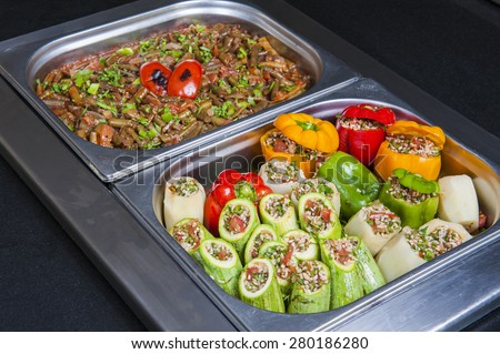 Closeup detail of dolma stuffed vegetables and green beans on display at an oriental restaurant buffet - stock photo