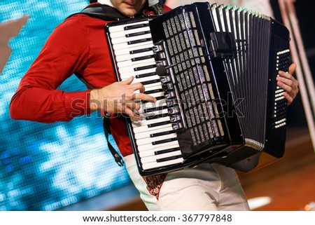 Closeup detail of hands playing a black accordion instrument - stock photo