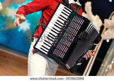 Closeup detail of hands playing a black accordion instrument