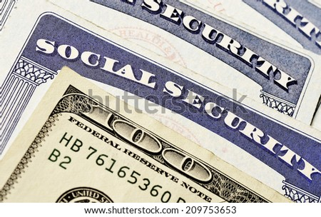 Closeup detail of several Social Security Cards and cash representing finances and retirement