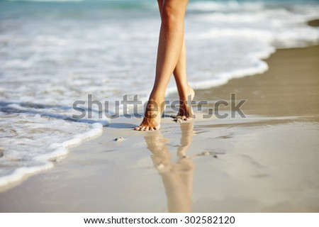 Closeup detail of woman legs and feet walking on the sand of the beach with the sea water in the background. Vacation holiday concept  - stock photo