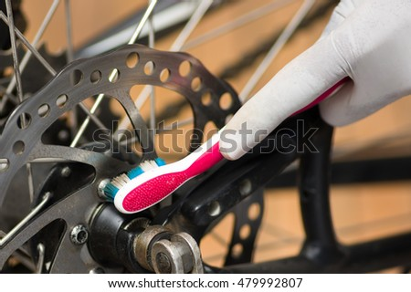 Closeup detailed look at bicycle wheel gear shifting mechanics during maintenance repairs, toothbrush brushing over parts