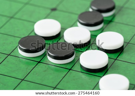 closeup discs on green Reversi board (Othello) - stock photo