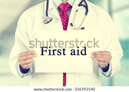Closeup doctor hands holding white card sign with first aid text message isolated on hospital clinic office background. Retro instagram style filter image - stock photo