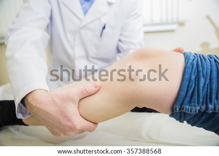 closeup doctor the traumatologist examines the patient the patient's leg - stock photo
