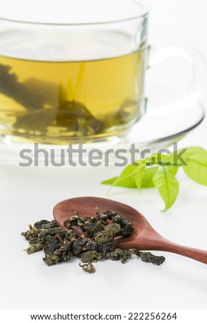 closeup dried green tea leaf with a cup of green tea