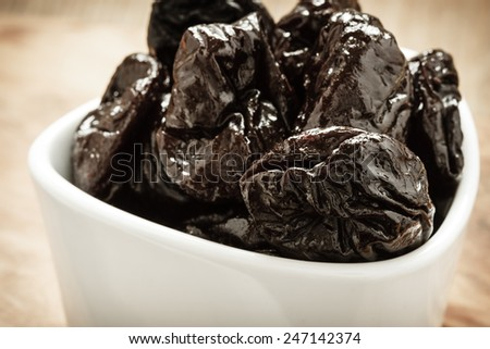 Closeup dried plums prunes fruits  in white bowl on wooden rustic table background