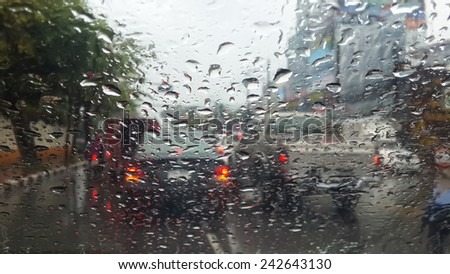 Closeup drops of rain that fell on the other side of the glass during the rush hour traffic. When the need to work to keep up. - stock photo