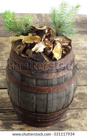 closeup dry mushrooms boletusin wodden barrel - stock photo