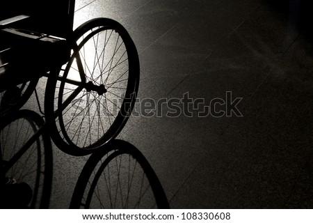 Closeup empty wheelchair on dark background and shadow - stock photo