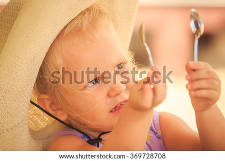closeup European cute little blond girl in hat shows two tea spoons against sand - stock photo