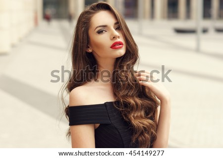 Closeup face fashion portrait of young beautiful pretty stylish girl with long curly brunette hair and red lips posing in city