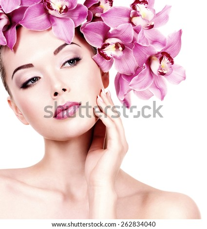 Closeup face of an young beautiful woman with a purple eye makeup and lips. Pretty adult girl with flower near the face.  - isolated on white background - stock photo