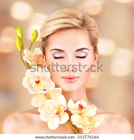 Closeup face of an young woman with health skin and flowers at face. Beauty treatment concept.