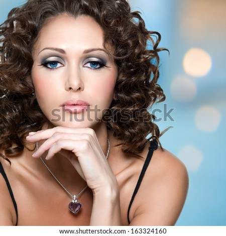 Closeup face of  beautiful adult woman with long curly hairs posing at studio - stock photo