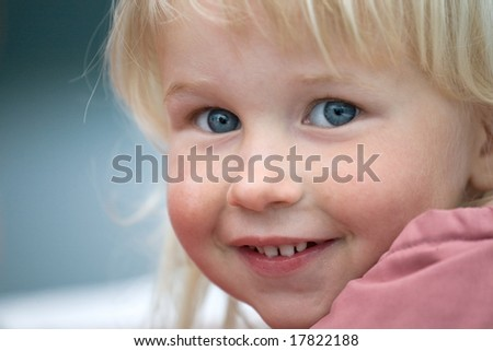 closeup face of beautiful smiling grey-eyed infant girl