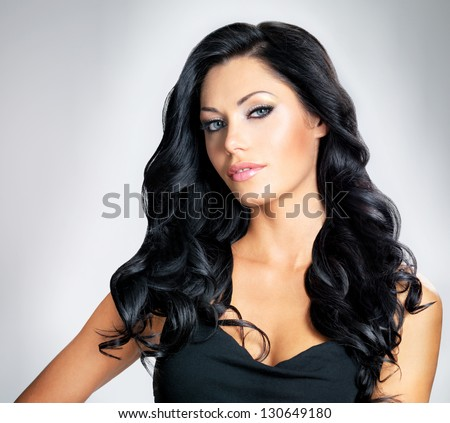 Closeup face of beautiful woman with long black curly hairs at studio