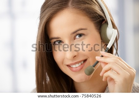 Closeup facial portrait of smiling beautiful call center operator woman with headset.? - stock photo