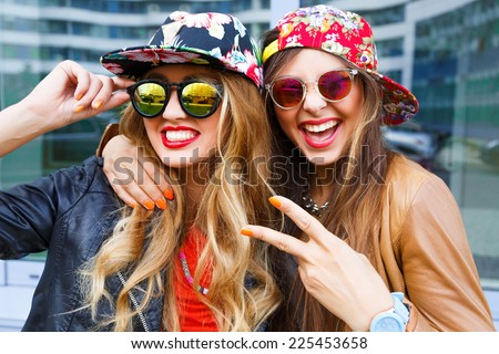 Closeup fashion lifestyle portrait of two pretty best friends girls, wearing bright swag style floral hats, mirrored sunglasses, having fun and make crazy funny faces. Two sisters posing on party. - stock photo