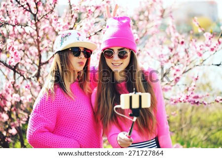 Closeup fashion lifestyle portrait of two young pretty beautiful friends in the lush spring garden on a sunny day. Cheerful friends, having fun together, joy and making selfie with self monopod.  - stock photo