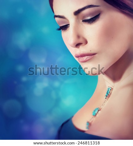 Closeup fashion portrait of a gorgeous stylish beautiful woman on blur blue background, attractive woman with perfect makeup looking down, luxury beauty salon theme - stock photo