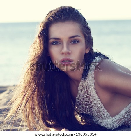 closeup fashion portrait of young sexy beautiful woman lying at beach and looking in camera - stock photo